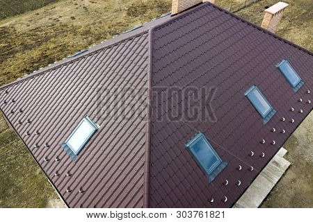 Aerial Top View Of Building Steep Brown Shingle Roof, Brick Chimneys And Small Attic Windows On Hous