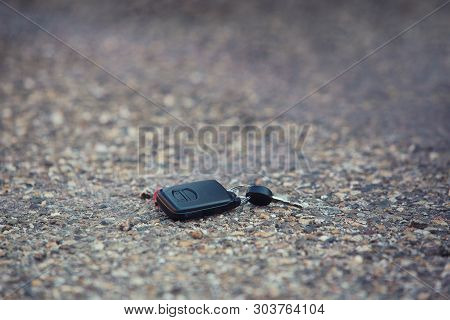 Car Key Fall On The Asphalt Road. Driver Lost His Vehicle Keys. Misfortune Concept.