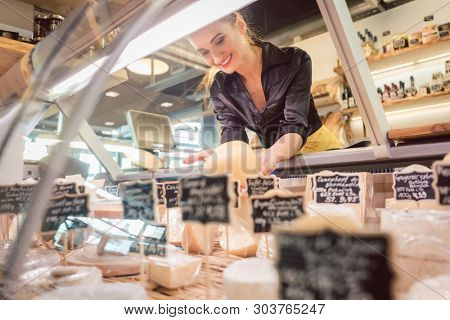 Shop clerk woman sorting cheese in the supermarket display to sell it