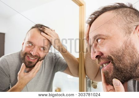 Happy Man Looking At His Hair In Bathroom Mirror. Seeing Improvement Of Hairline. Male Haircare Conc