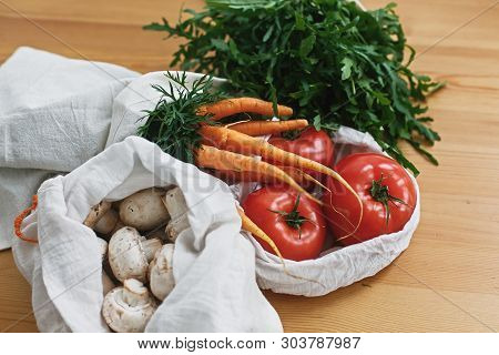 Fresh Vegetables In Eco Cotton Bags On Wooden Table In Kitchen. Carrots,tomatoes, Arugula, Mushrooms