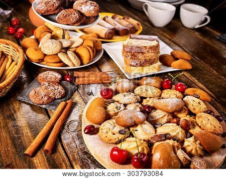 Oatmeal cookies and sand chocolate cake with cherry berry and crispy wafer rolls with cream on cutting board on wooden table in rustic style. Limitations for diabetics. Cherry in powdered sugar.
