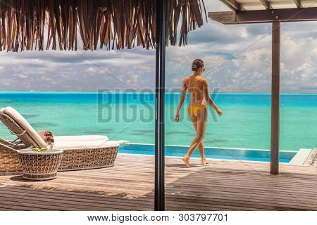 Luxury Bora Bora resort hotel woman walking on her private terrace deck of overwater bungalow villa with infinity pool view on turquoise ocean - honeymoon's suite.
