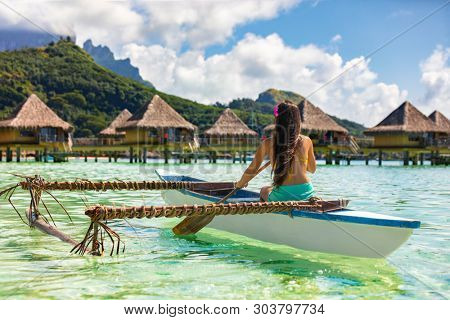 Outrigger Canoe - woman paddling in traditional French Polynesian Outrigger Canoe for recreational activity and watersport competition. Bora Bora with  overwater bungalow resort hotel sport lifestyle