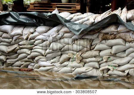 Temporary Wall Made Of White Sandbags And Thick Black Nylon Used As Flood Protection To Prevent Floo