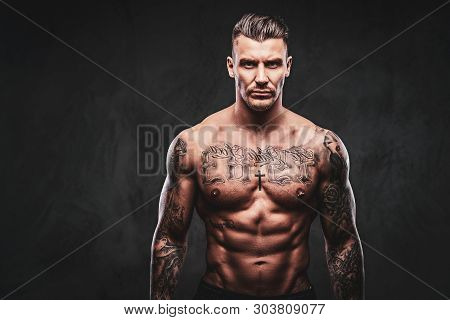 Portrait Of A Tattooed Muscular Shirtless Man With Stylish Hair Posing At The Camera On A Dark Backg