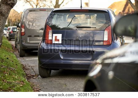 Blue Hatchback Car With A Learner Driver Sign At The Rear, Parking At The Side Of The Road, Parking