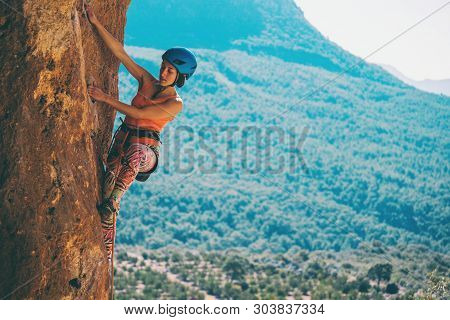 A Girl In A Helmet Climbs A Rock. Woman Overcomes Challenging Climbing Route On The Background Of Be