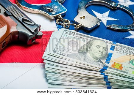 Withdrawn Money And Weapons On The American Flag - A Crime And Punishment Concept Photo