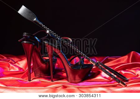 Adult Sex Games. Kinky Lifestyle. Spank And A Pair Of Black High-heeled Shoes On The Red Linen. Bdsm