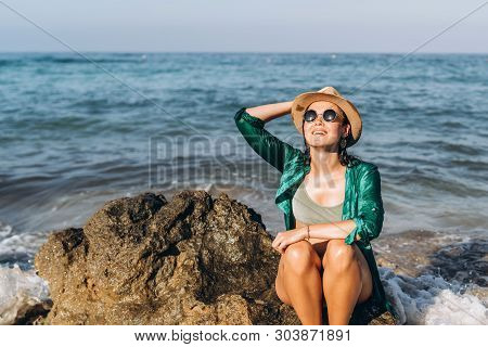 Pretty pan asian travel girl relaxing on the beach at the sea in green pareo poster