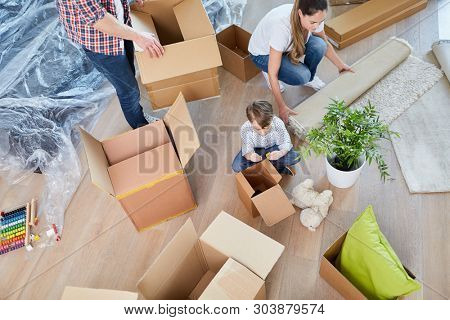 Family unpacks moving boxes when moving into the new home or house