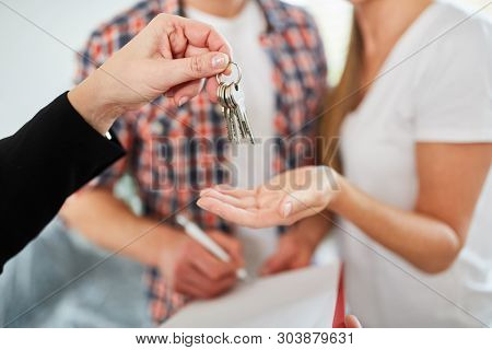Broker hands keys for apartment or new home as a home to couple