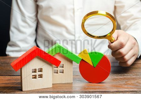 Businessman Holding A Magnifying Glass Over A Pie Chart And A Wooden Houses. Concept Analysis Of The