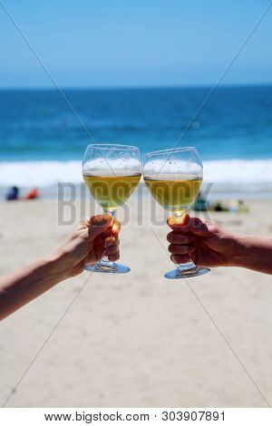 Wine at the beach. Wine Toast with ocean and sand background. Two friends toast to friendship at the beach with white wine.