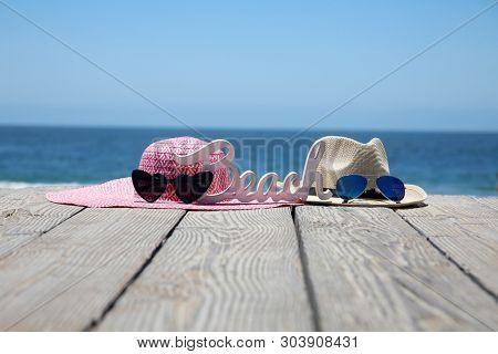Summer Beach Scene. Sun Hats, Sun Glasses and a BEACH Sign. Beach Board walk with fashion clothes at the beach.