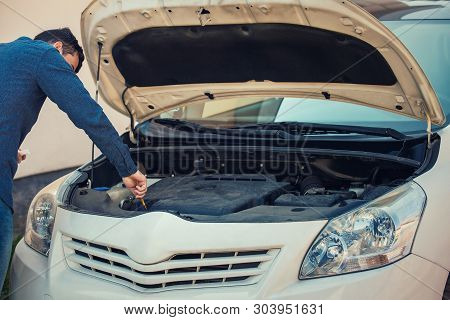 Driver Check Oil Level In The Car Engine. Vehicle Repair Service, Auto Mechanic Job. Young Man Motor