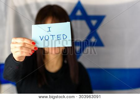 Young Woman Holding Ballot Front Of Face On Israeli Flag Background. Text I Voted On Voting Paper. I