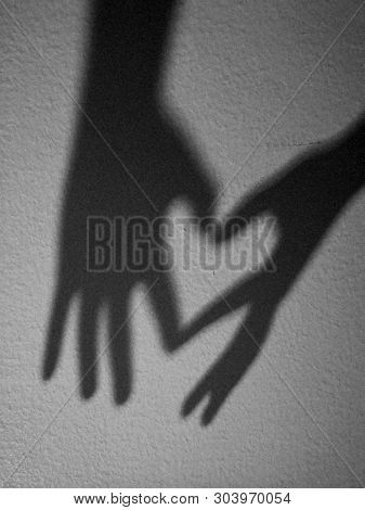 Love sign formed by shadow of hand