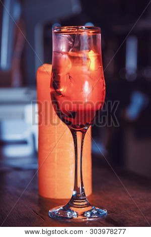 red cocktail in a tall glass on the bar. close-up