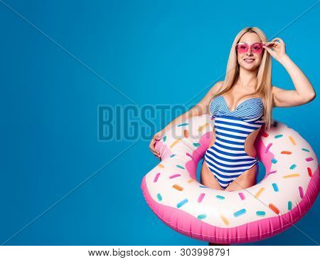 Image of happy woman in striped bathing suit and pink glasses with life preserver donut on blue empty background