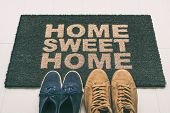 Door mat Shoes at front entrance of condo apartment. Written welcome sign Home Sweet Home welcoming homeowners at new house moving in couple's pairs of sneakers lying on the floor. poster