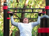 The young man performs a sports exercise pull-up on the bar. Training on the street to develop the strength of the back muscles, deltoids, triceps and biceps. poster