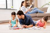 family, fatherhood and leisure concept - father spending time with his little daughters drawing in sketchbooks by crayons and lying on floor at home poster