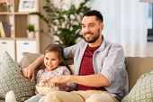 family, fatherhood and people concept - happy father and daughter with popcorn watching tv at home poster