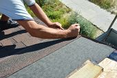 Roofer contractor gluing waterproof membrane on wooden roof top surface with black bitumen  spray on tar and laying asphalt shingles, Roofing construction. poster