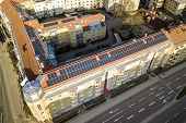 Top view of blue solar photo voltaic panels system on high apartment building roof top on sunny day. Renewable ecological green energy production concept. poster