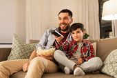 family, childhood, fatherhood, technology and people concept - happy father and little son with popcorn and remote control watching tv at home in evening poster