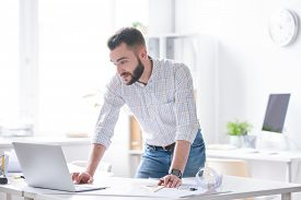 Young confident businessman or architect in shirt and jeans looking at laptop display while bending over desk on working day