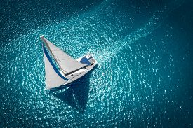 Regatta Sailing Ship Yachts With White Sails At Opened Sea. Aerial View Of Sailboat In Windy Conditi
