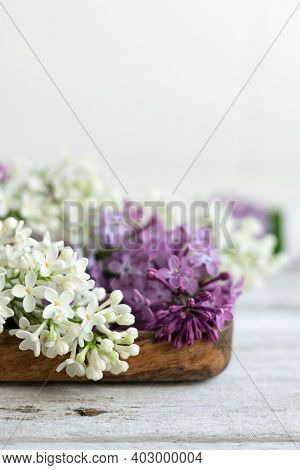 Lilac Flowers Lie On A Wooden Tray. White And Lilac Flowers. Light Coloured Background And Minimalis