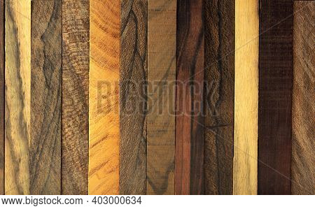 Wood background. Various kinds of exotic woods in vertical strips.