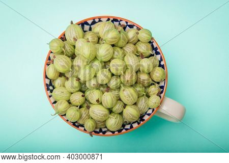 Fresh Gooseberries In Glass Bowl On Turquoise Stone Slate Background. Top View.