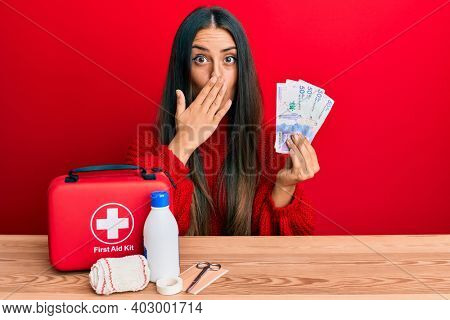 Beautiful hispanic woman with first aid kit holding colombian pesos covering mouth with hand, shocked and afraid for mistake. surprised expression