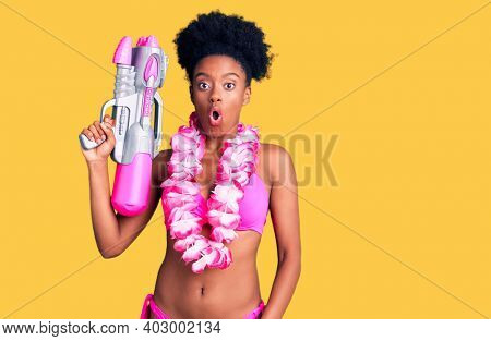Young african american woman wearing bikini and hawaiian lei holding water gun scared and amazed with open mouth for surprise, disbelief face