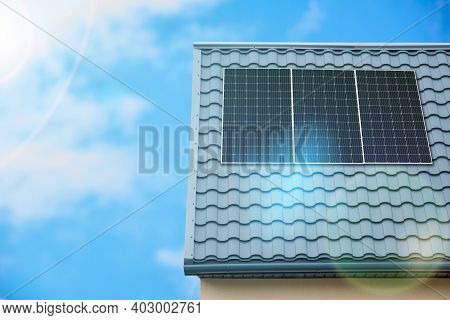 Solar Cell Panel On Metal Roof Of House. Photovoltaic Solar Modules With The Rays Of Sun. Alternativ