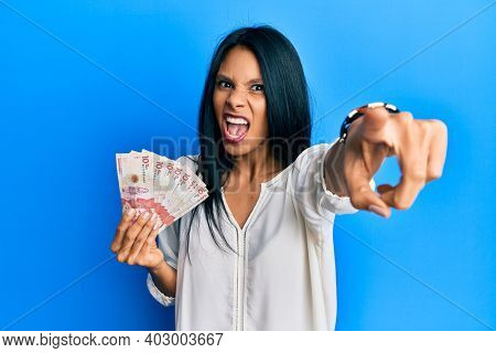Young african american woman holding 10 colombian pesos banknotes pointing displeased and frustrated to the camera, angry and furious with you