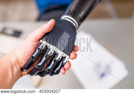 Handshake Between Hand Of Human And Robot Hand Isolated On Office Background