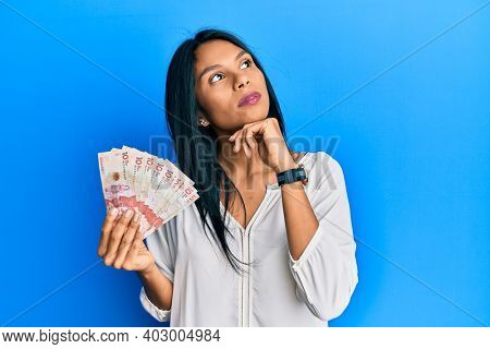 Young african american woman holding 10 colombian pesos banknotes with hand on chin thinking about question, pensive expression. smiling with thoughtful face. doubt concept.