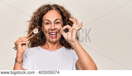 Middle age beautiful  woman eating sushi using wooden chopsticks over white background doing ok sign with fingers, smiling friendly gesturing excellent symbol