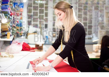 Fashion Designer Tailor Or Sewer In Workshop Studio Designing New Collection Clothes.