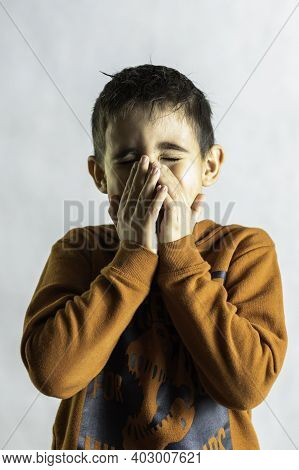 Boy Photographed In The Middle Of A Sneeze Covers His Face With His Hands Portrait Of A Boy While Ha