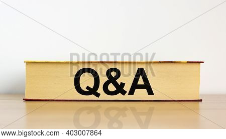 Questions And Answers Symbol. Book With Word 'q And A, Questions And Answers' On Beautiful Wooden Ta