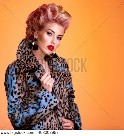 Beautiful woman with style hairstyle. White woman with bright colored makeup. Fashionable young woman is in the spotted fur coat. Stunning blonde girl. Bright eye makeup. Attractive sexy model poses