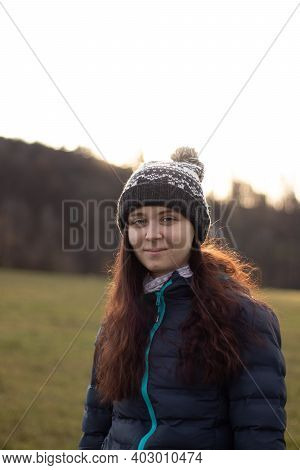 Pleasant Smile Of A Young Girl Aged 20-24 At Sunset. Girl With Brown Hair And A Beautiful Black And
