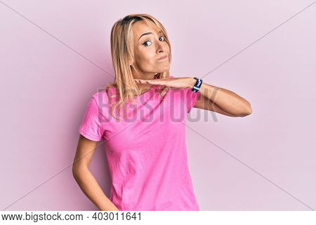 Beautiful blonde woman wearing casual pink tshirt cutting throat with hand as knife, threaten aggression with furious violence